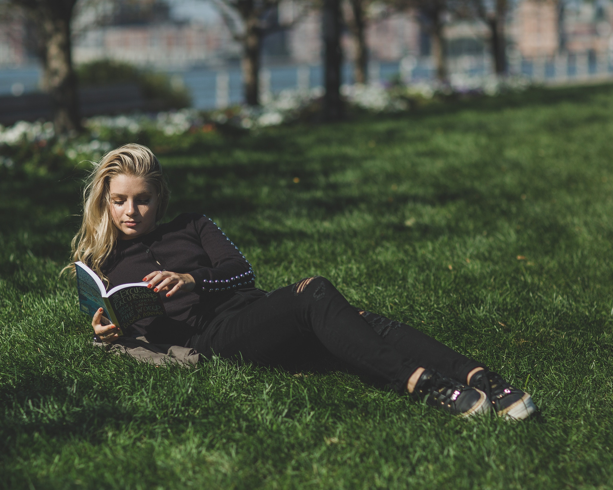 woman lying in green grass with a book